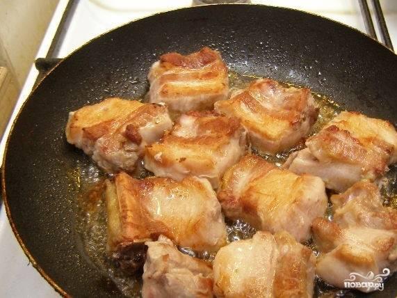 4. Разогрейте растительное масло на сковородке. Переложите в нее кусочки свинины. Обжарьте с каждой стороны до появления корочки. Выложите свинину в казанок или воспользуйтесь кастрюлей с толстым дном.