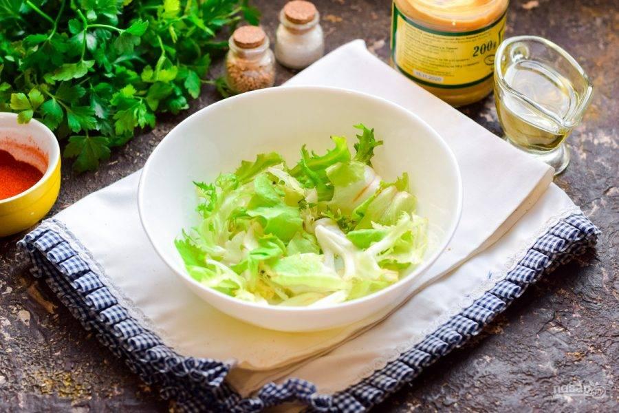 Салатные листья сполосните и просушите, порвите руками и переложите в глубокую тарелку.