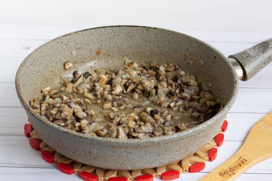 Лук очистите, помойте, измельчите. Грибы помойте и мелко нарежьте. В небольшом количестве растительного масла обжарьте лук до прозрачности, затем добавьте грибы. Жарьте ещё 2-3 минуты.