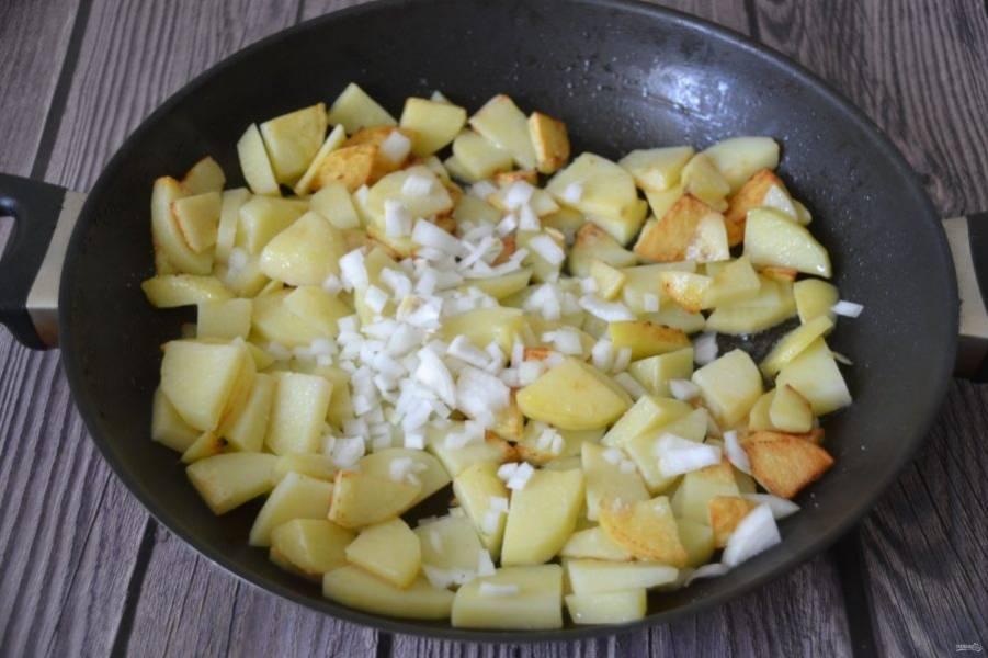После того, как картошка поджарится с одной стороны, помешайте, посолите, добавьте вторую половину лука, жарьте еще 10 минут.