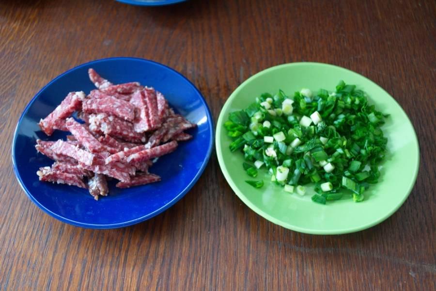 Колбасу очистить и нарезать соломкой. Измельчите зеленый лук.