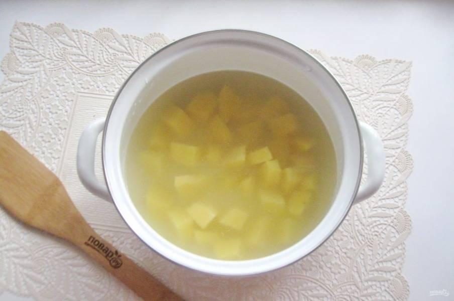 Картофель очистите, помойте и нарежьте произвольно. Выложите в кастрюлю с водой. У меня был нежирный куриный бульон. Начинайте варить суп.