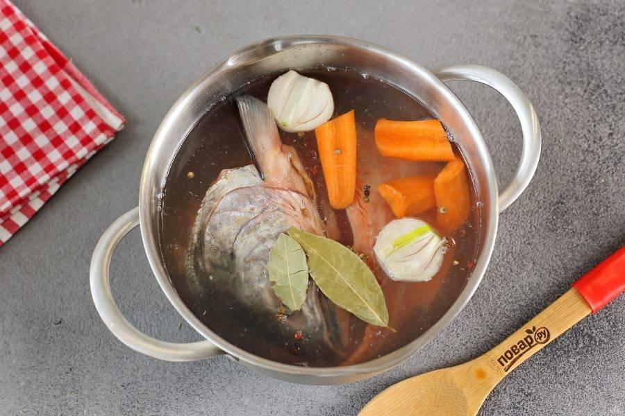 Промойте рыбный набор для супа. Если у вас набор с головой, то обязательно удалите жабры. Переложите части рыбы в кастрюлю, добавьте лавровый лист, перец горошком, разрезанные на части лук и морковь. Налейте воду, доведите до кипения, уберите пену и при слабом кипении варите 20 минут.