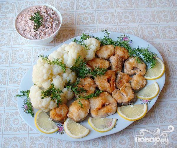 4.Жареную рыбу выкладываем на блюдо, так же и вареную капусту. Украшаем зеленью и лимоном. Соус подаем отдельно.