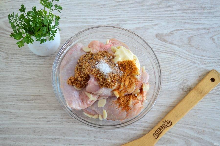 Куриные бедра промойте и обсушите бумажными полотенцами. Сложите бедра в миску, добавьте майонез, горчицу (лучше брать в зернах, но можно и обычную), порезанный чеснок, соль и приправу.