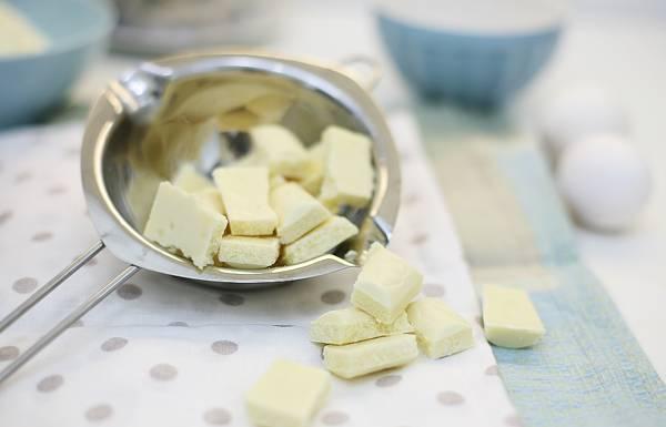 2. Плитку белого шоколада разломайте на кусочки и растопите на водяной бане. Добавьте в тесто, чуть-чуть остудив. Использовать можно и черный шоколад, однако с белым бисквит будет нежнее.