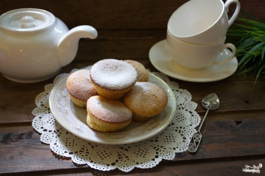 Еще одной столовой ложкой теста закройте варенье, чтобы его не было видно на уровне сырого теста. Разогрейте духовку до 160 градусов. Выпекайте кексы в духовке до 15 минут. Извлеките кексы из формочек. Дайте им остыть. Присыпьте кексы сахарной пудрой и подавайте к столу.