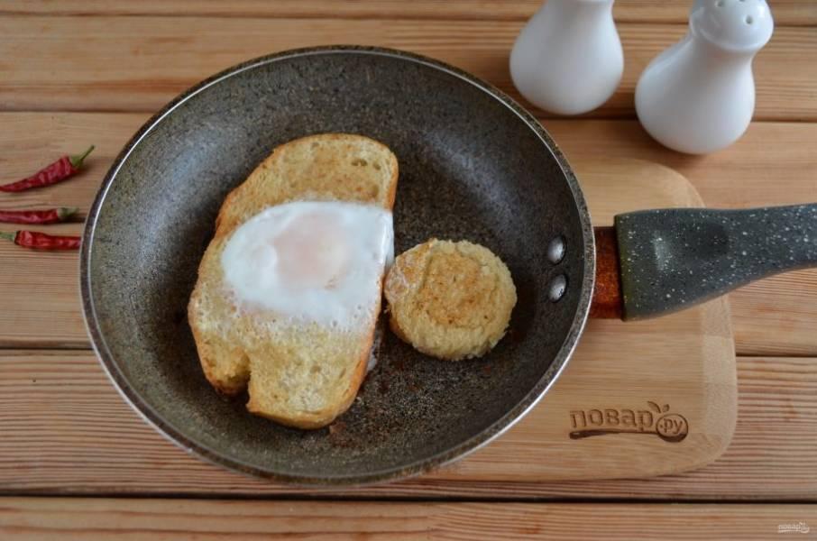 Вбейте яйцо и сделайте небольшой огонь. Накройте плотно крышкой, это позволит белку свернуться, а желтку остаться жидким. Жарьте пару минут всего.