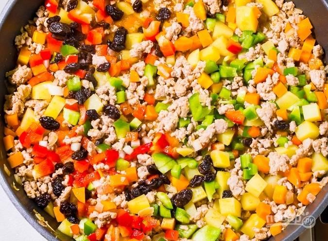 Далее добавьте морковь и картофель без воды, а также перец и изюм. Влейте томатный и соевый соус. Всыпьте соль и перец.