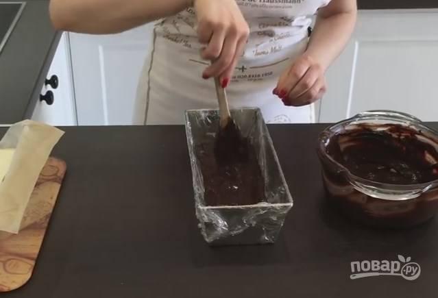 8. Извлеките запеченный творог из формы и поставьте остывать. Форму со всех сторон оберните пищевой пленкой и вылейте в нее половину шоколадной помадки. Разровняйте.