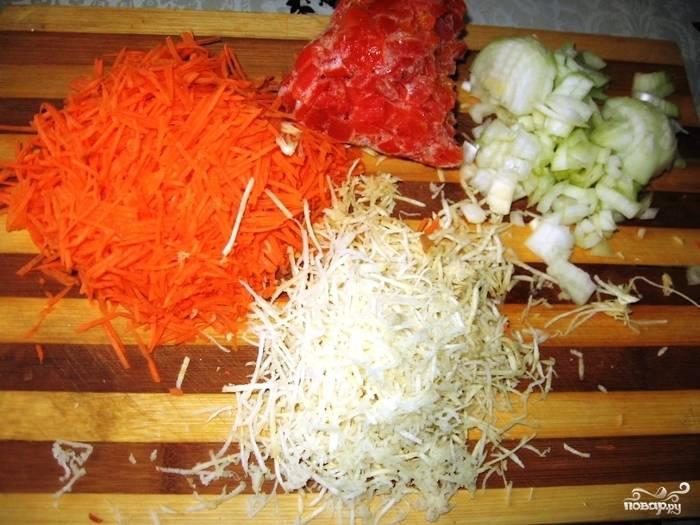 Пока варится мясо, можете заняться другими продуктами. Мелко порежьте лук кубиками, перец — так же. Морковку и петрушку натрите на терке или соломкой мелкой порежьте.