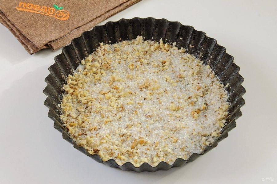 Дно формы для выпечки застелите пергаментом и хорошо смажьте маслом. Грецкие орехи измельчите, смешайте с оставшимся сахаром и распределите равномерно по дну формы.