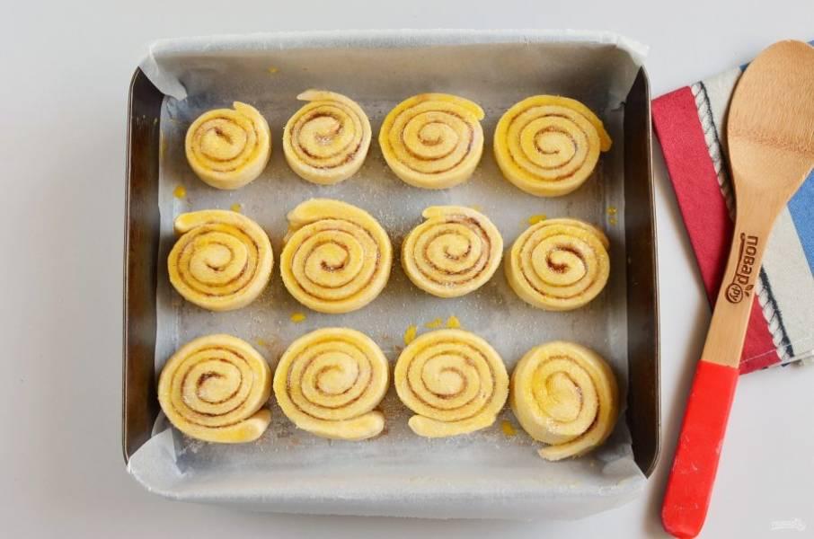 Смажьте булочки желтком, сверху притрусите сахаром, для вкусной сладкой корочки.