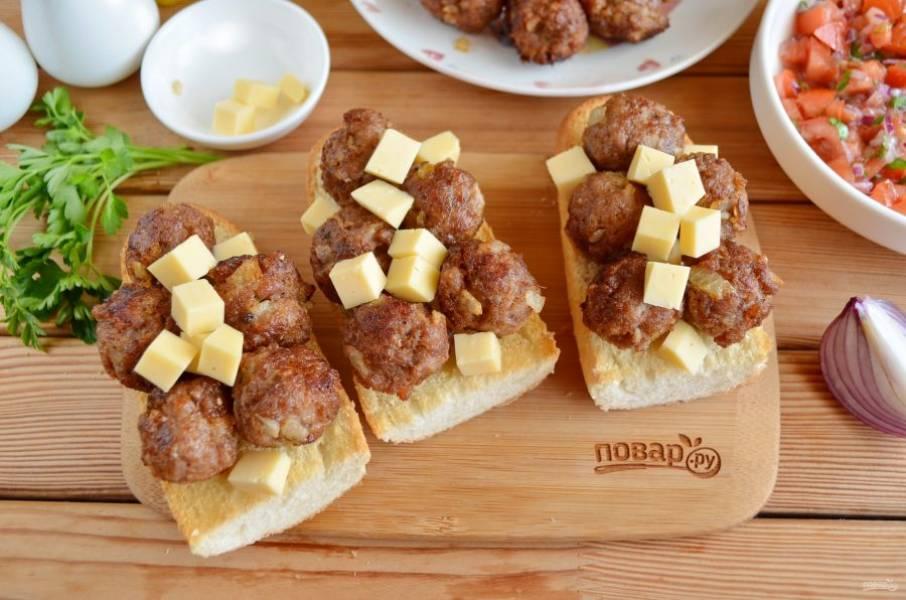 На булочки уложите сверху мясные шарики, кусочки сыра и отправьте в духовку до расплавления сыра.