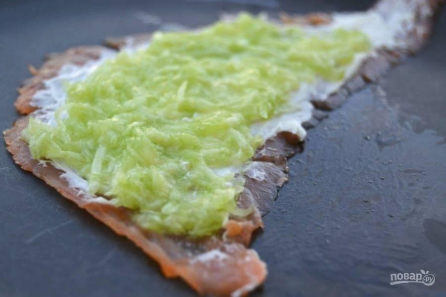 4.Поверх сыра уложите тертый огурец и распределите его равномерно.