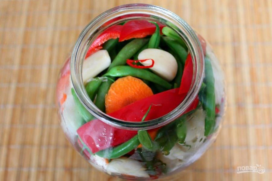 На дно банки кладем листья смородины, можно также добавить листок хрена и вишни. Укладываем все подготовленный овощи, чередуя их произвольно.