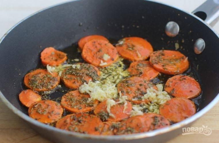 Добавьте к моркови пропущенный через пресс чеснок и травы. Затем перемешайте и обжаривайте ингредиенты еще семь минут.