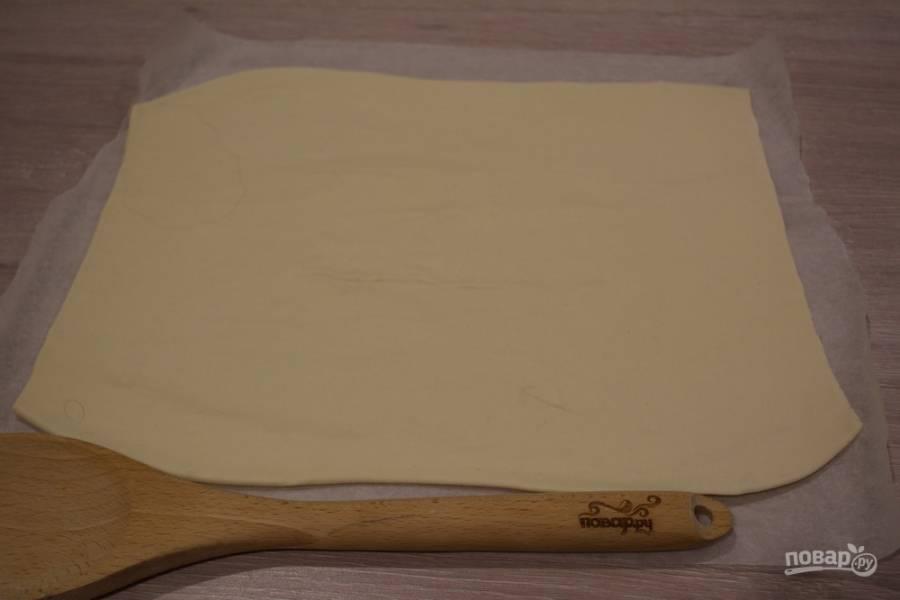 Перенесите пласт теста на бумагу для выпечки.