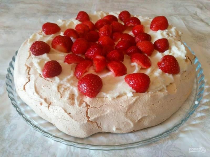 Подготовьте ягоды клубники, промойте их и разрежьте на части, разложите поверх крема и по желанию присыпьте сахарной пудрой.
