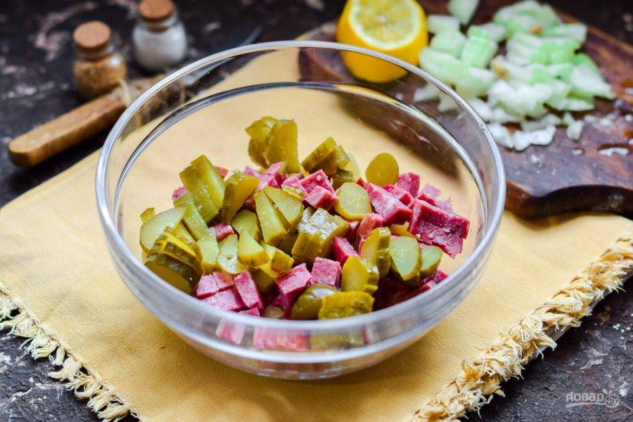 Соленые огурцы нарежьте кубиками и добавьте в салат.
