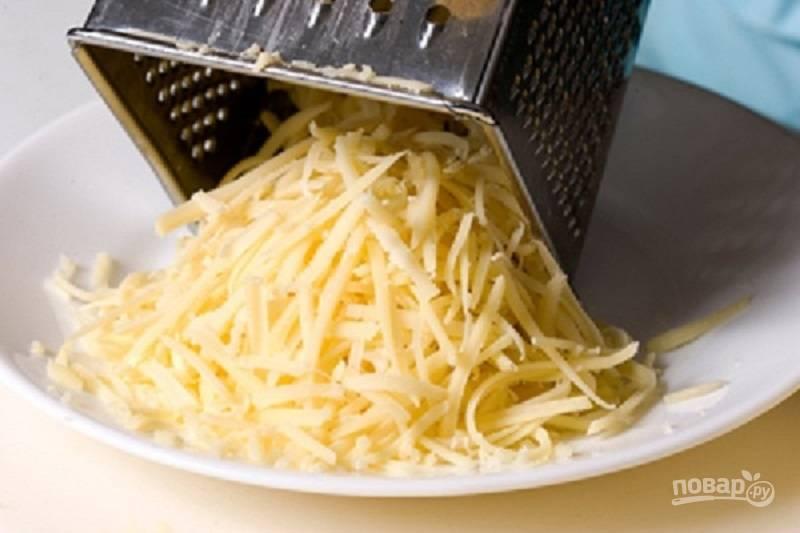 Сыр натрите на крупной терке, выложите четвертым слоем и смажьте его майонезом.