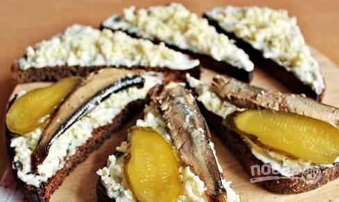 На хлеб с соусом и яйцом выложите по одной рыбке и по кусочку огурчика. Украсьте бутерброды перышками зеленого лука и подавайте их к столу.
