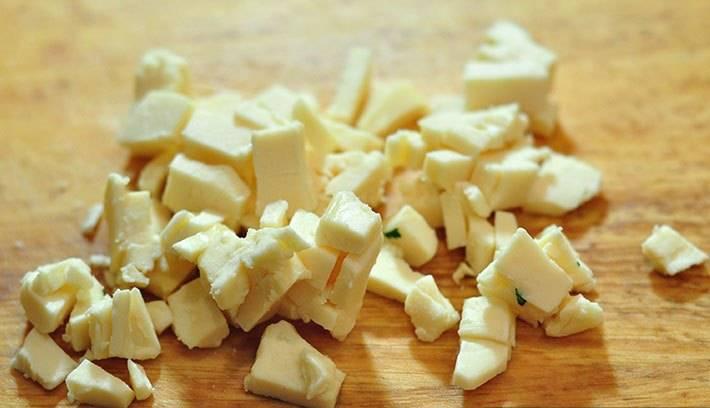 Плавленный сыр нарежьте кубиками и добавьте к остальным ингредиентам.