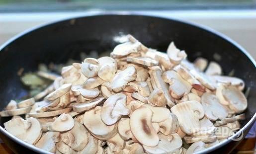 Шампиньоны хорошо моем и нарезаем пластинками. Отправляем их на сковороду к луку и жарим 5-6 минут на маленьком огне. Несколько обжаренных грибных ломтиков оставим для подачи.