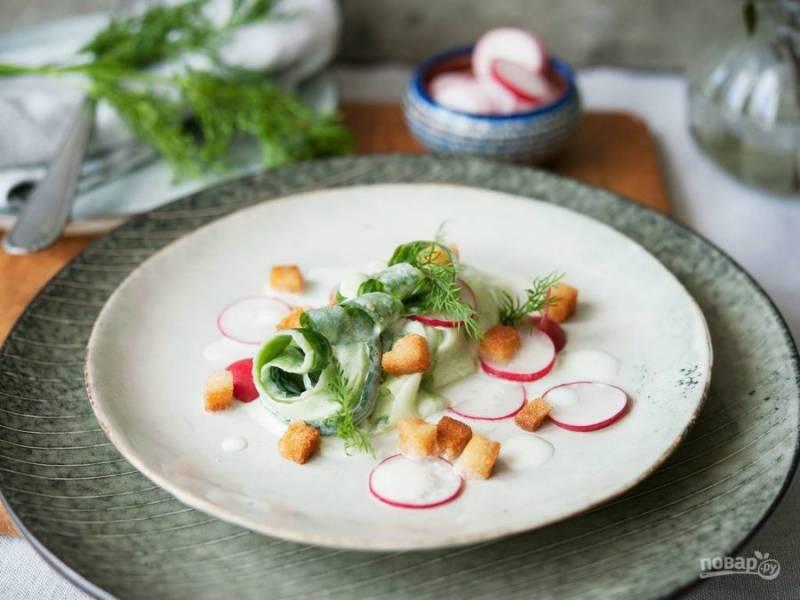 4. На тарелку выложите огурец, редис и крутоны. Покройте их заправкой. Салат готов! Приятного аппетита!
