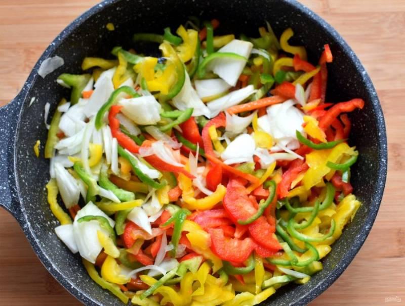 Добавьте к моркови тонко нарезанный лук и перцы. Прогрейте при помешивании минутку-другую до появления яркого аромата.