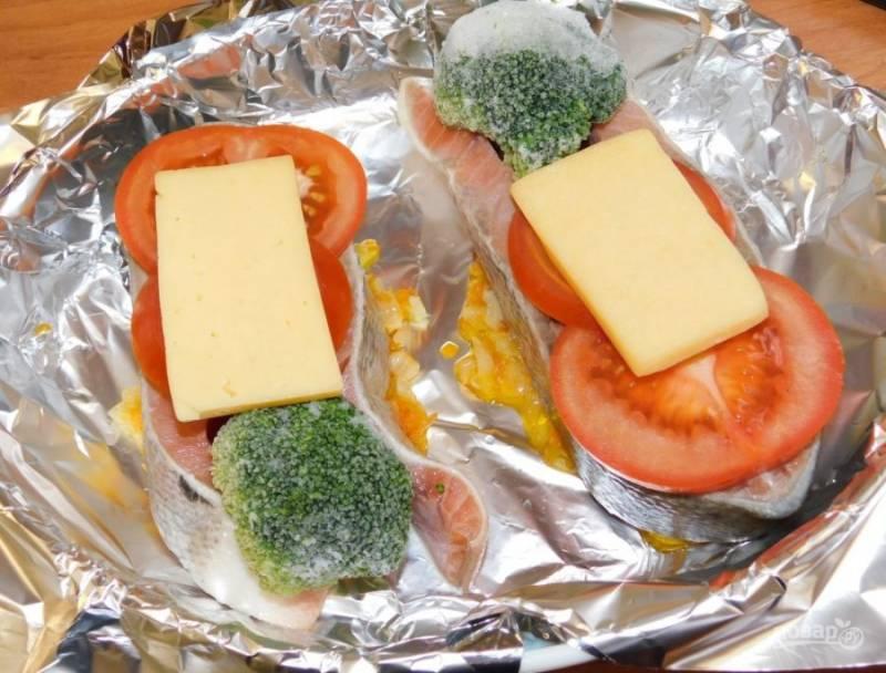 Сверху положите кусочек сыра. Заверните рыбу с овощами в фольгу и поставьте в духовку, разогретую до 200 градусов, на 20 минут. Затем фольгу откройте и запекайте еще минут на 15-20.