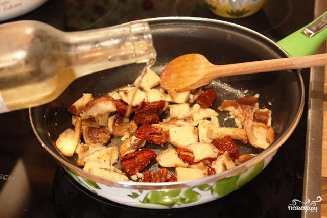 Когда грибы и чеснок подрумянятся - вливаем вино, добавляем сушеные помидоры и перемешиваем.