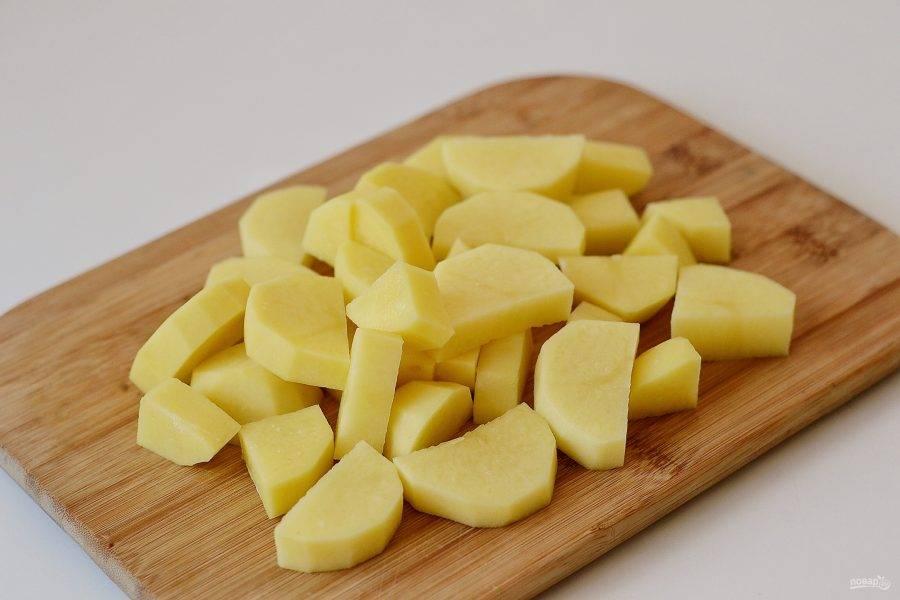 Картофель помойте, очистите от кожуры, затем нарежьте дольками.