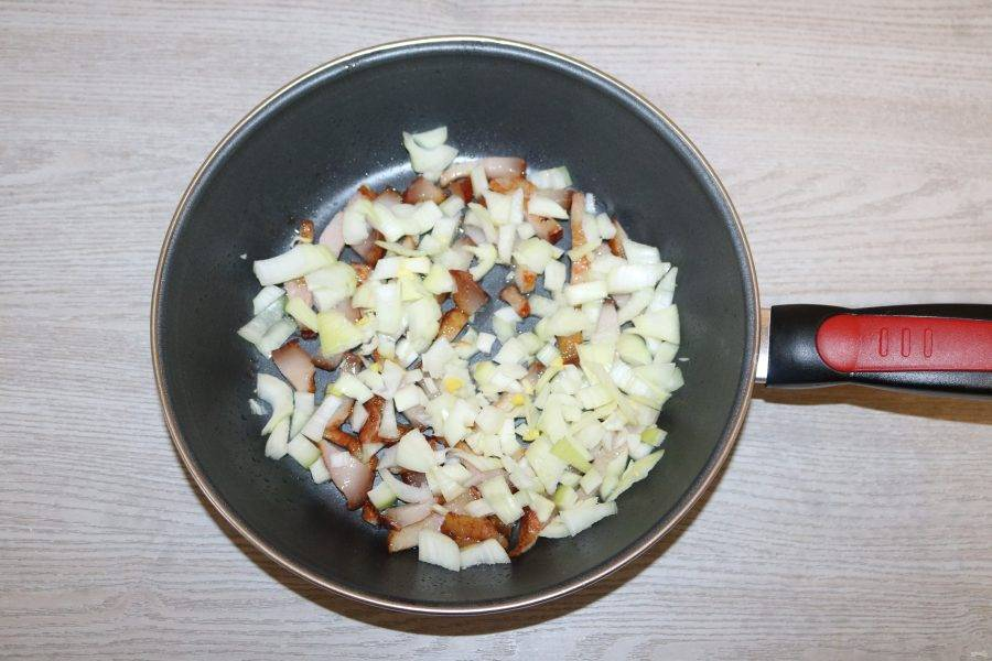 К бекону добавьте лук, обжаривайте вместе.
