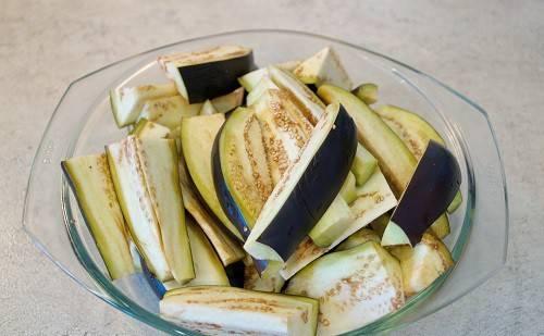 Для начала промываем баклажаны, удаляем у них плодоножку и нарезаем баклажаны вдоль на четыре части.