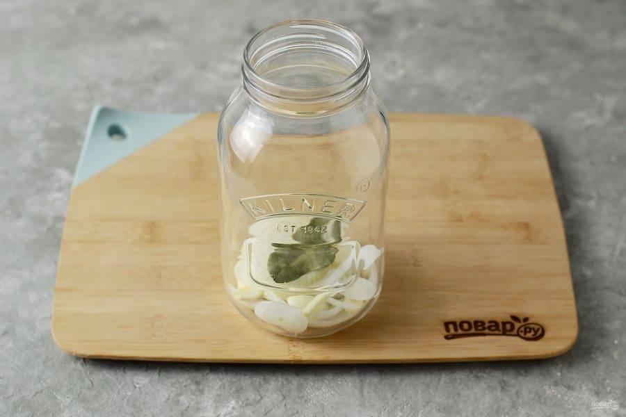 Выложите лук и чеснок в чистую, заранее стерилизованную банку. Добавьте лавровый лист.