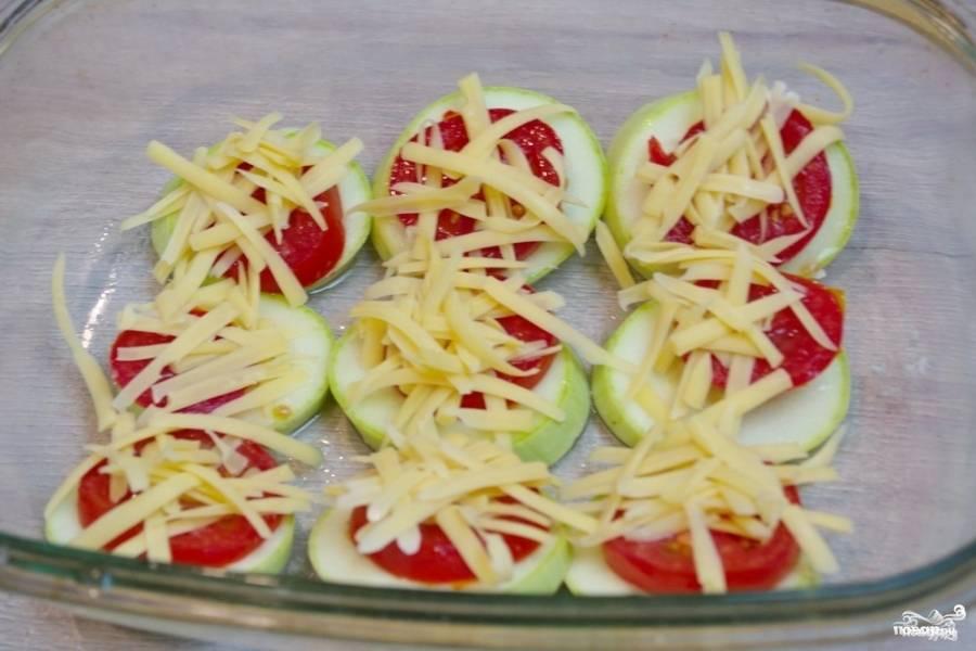 На крупной терке натрите твердый сыр. Выложите его на каждый кусочек помидора.