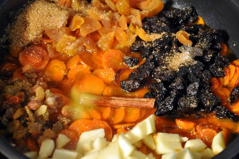 3. Говядина пусть жарится, вы ее периодически перемешивайте. А пока займитесь приготовлением цимеса. Понадобится кастрюлю или высокая сковорода. Морковь нарежьте кружочками-монетками. Слегка обжарьте на масле в течение 4-5 минут. Затем к моркови выложите изюм, курагу, чернослив, почищенное и порезанное полудольками яблоко. Добавьте мед, сахар, корицу, гвоздику и залейте водой. Перемешайте. Включите слабый огонь, накройте крышкой и тушите час, периодически помешивая.