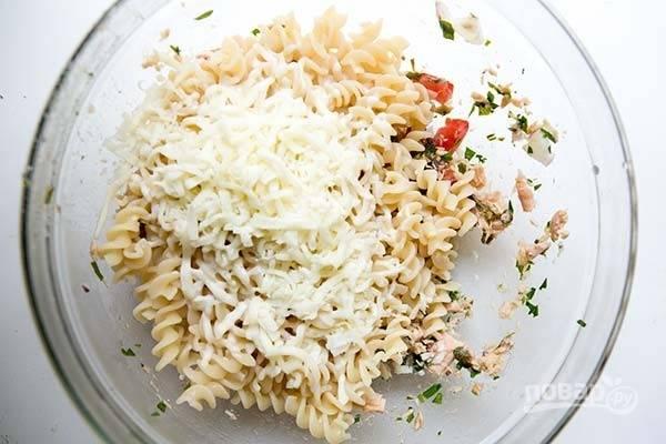 2.Выложите отварные макароны в миску к остальным ингредиентам, добавьте тертый сыр. Если макароны сухие, влейте 50 миллилитров жидкости, в которой варили макароны.