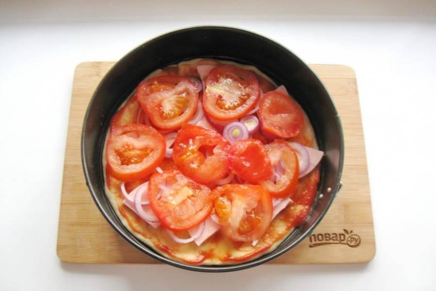Крупный помидор помойте и нарежьте кружками. Выложите на лук.