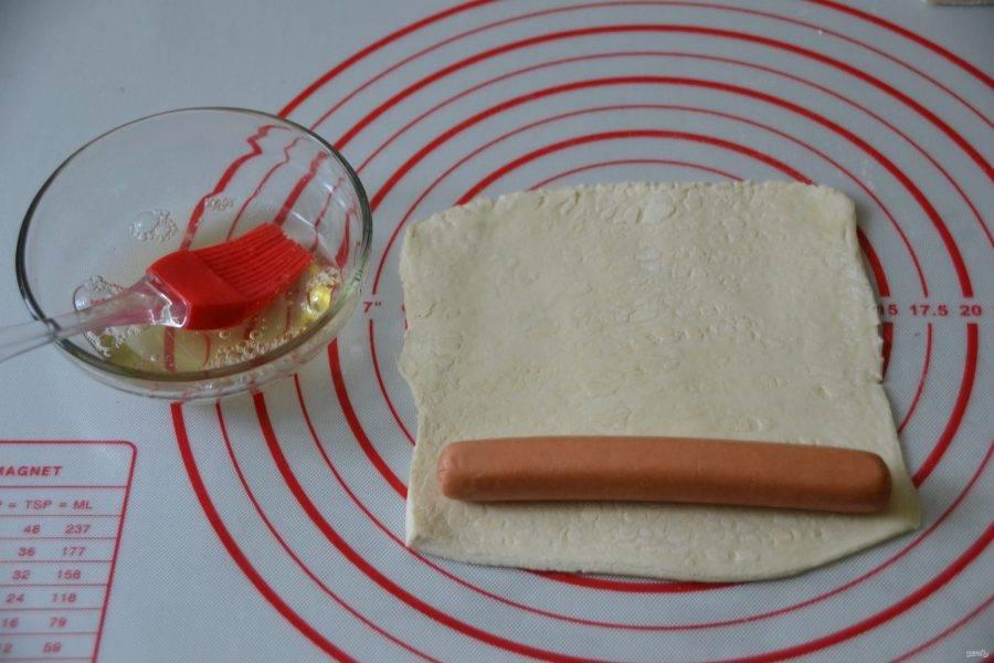 Раскатайте четвертинку теста в пласт, размером чуть больше сосиски. Смажьте тесто взболтанным белком, заверните в него сосиску.