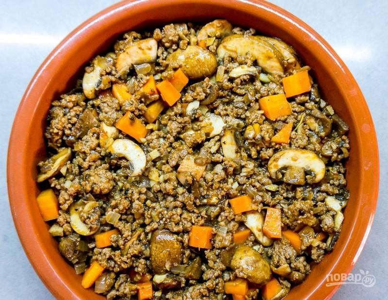 Форму для запекания смажьте маслом и всыпьте начинку из фарша и грибов.