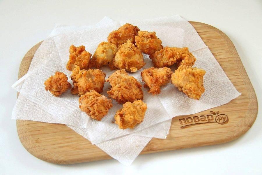 Поставьте на плиту глубокую сковороду или сотейник, налейте большое количество масла и, когда оно разогреется, опустите в него обваленные кусочки курицы. Масло должно полностью покрывать курицу. Жарьте примерно по 2-3 минуты с каждой стороны до золотистого цвета. Обжаренные кусочки выкладывайте на салфетку, чтобы убрать излишки жира. Пока жарится одна порция, трясем в пакете параллельно другую.