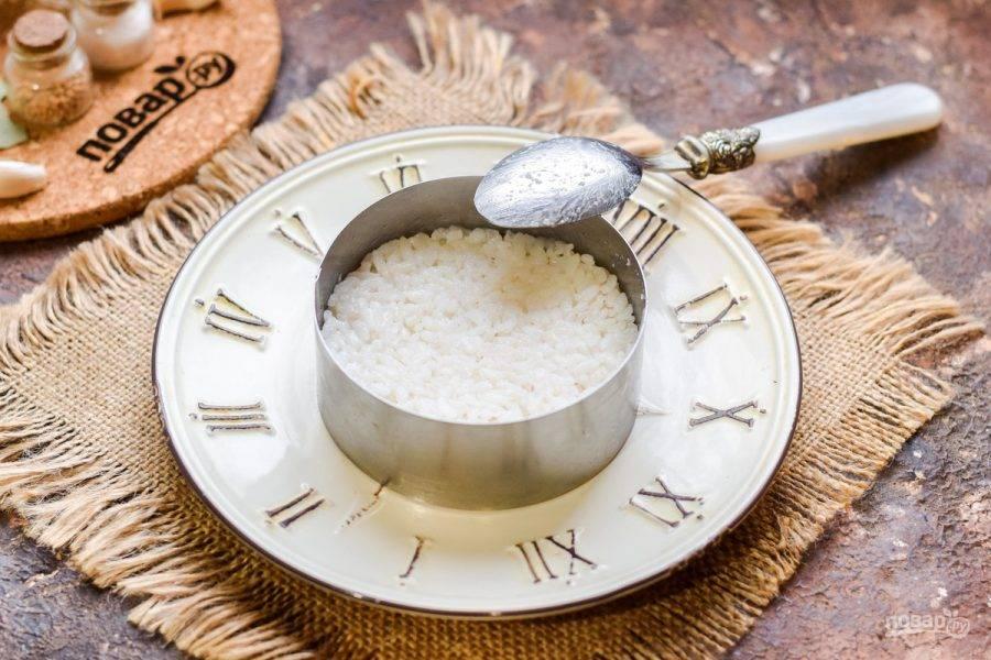 Подготовьте кольцо для салата. Выложите в форму первым слоем рис.