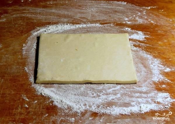2. Горсть муки высыпьте на рабочую поверхность, выложите тесто. Оно должно быть не слишком замороженным, чтобы с ним можно было легко работать. Раскатывать его вы можете как очень тонко, так и совсем немного, от этого будет зависеть толщины коржа. Ориентируйтесь также на размер вашей формы для запекания.