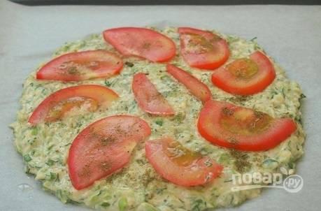Противень застилаем пергаментом и чуть смазываем растительным маслом. Выкладываем тесто в форме основы для пиццы. Раскладываем сверху тонкие ломтики помидора, посыпаем ароматными травами.