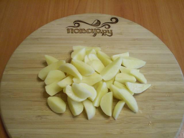 Порежьте дольками картофель.