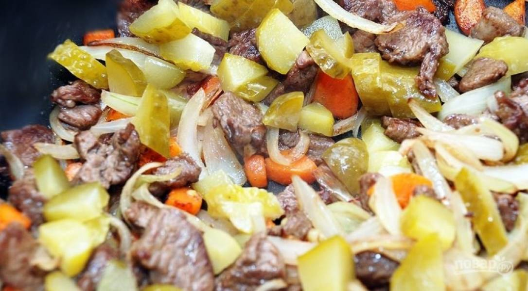 Постепенно добавляем к мясу овощи. Сперва отправляем на сковороду репчатый лук, затем морковь, острый перец, соленый огурчик.