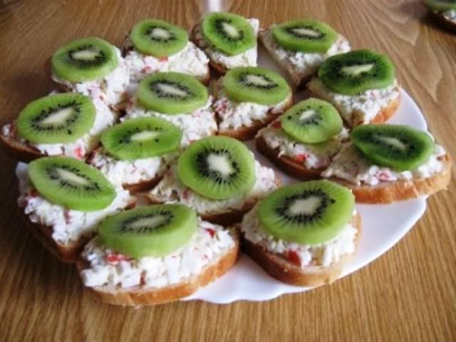 На каждый бутерброд положите по пластинке киви. Готовую закуску подавайте на стол.