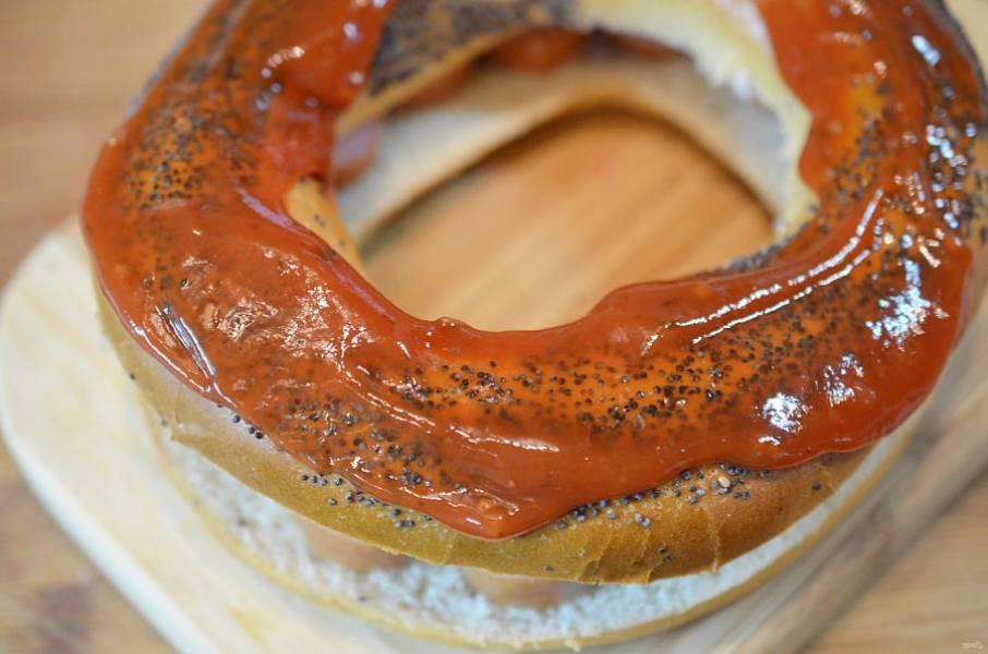 Накройте верхней частью бейгла и смажьте томатным соусом.